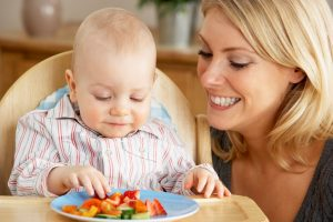 Mother Feeding Young Son In High Chair